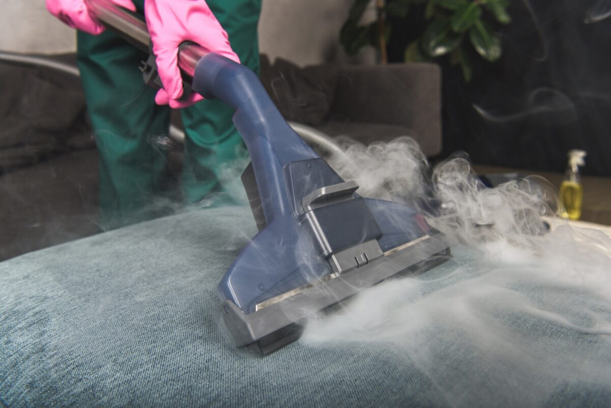 cropped shot of person cleaning sofa with vacuum cleaner, hot steam cleaning concept