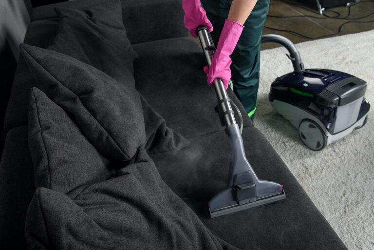 cropped shot of person cleaning sofa with vacuum cleaner, upholstery cleaning concept