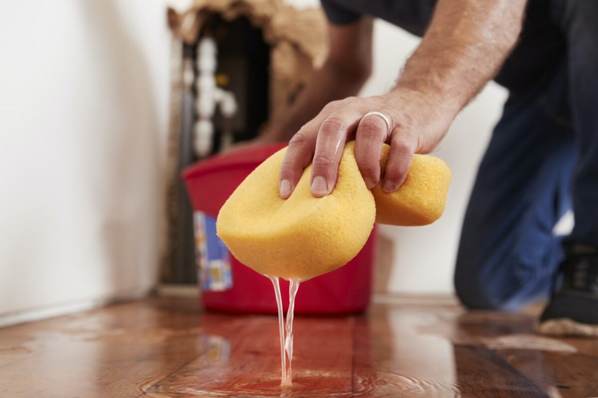 Man mopping up water from the floor with a sponge, detail