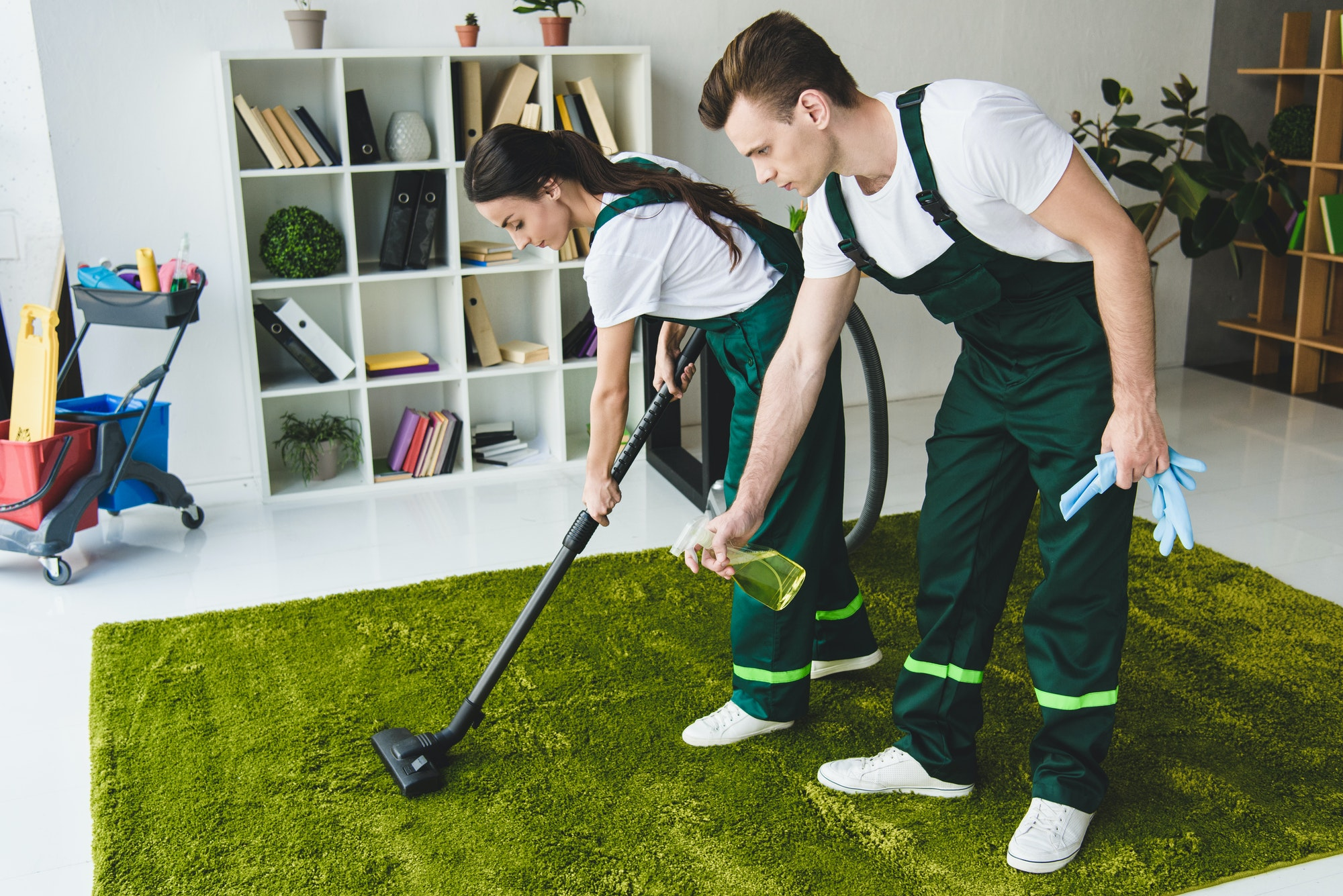 young cleaning company workers cleaning carpet with vacuum cleaner and detergent spray